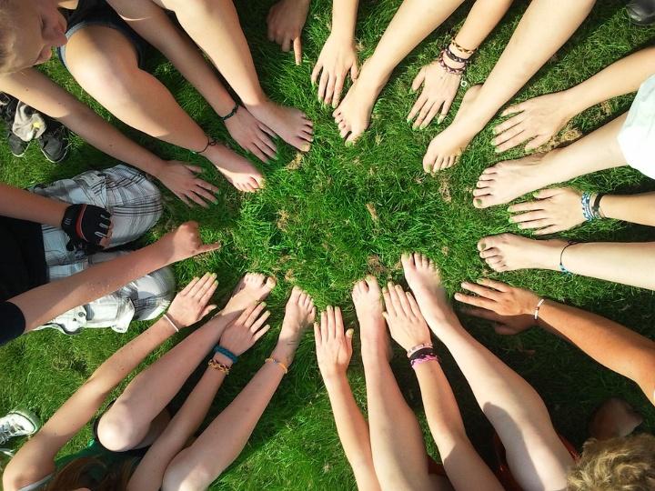 Auf dem Bild sind die Füße und Hände einer Gruppe von etwas zehn jungen Menschen zu sehen, die im Kreis auf einer Wiese sitzen. Es scheint Sommer zu sein. Viele tragen kurze Kleidung und sind barfuss. Ihre Hände und Füße bilden gemeinsam einen Kreis.