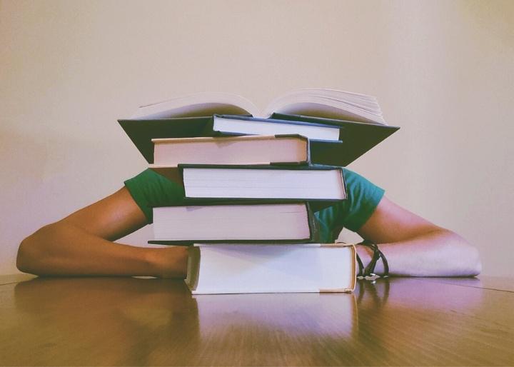 Auf einem Tisch steht ein Stapel Bücher. Das oberste Buch ist in der Mitte aufgeklappt. Hinter dem Stapel sitzt eine Person. Man sieht nur ihe Arme und Schultern. Der Kopf ist verdeckt von den Büchern.