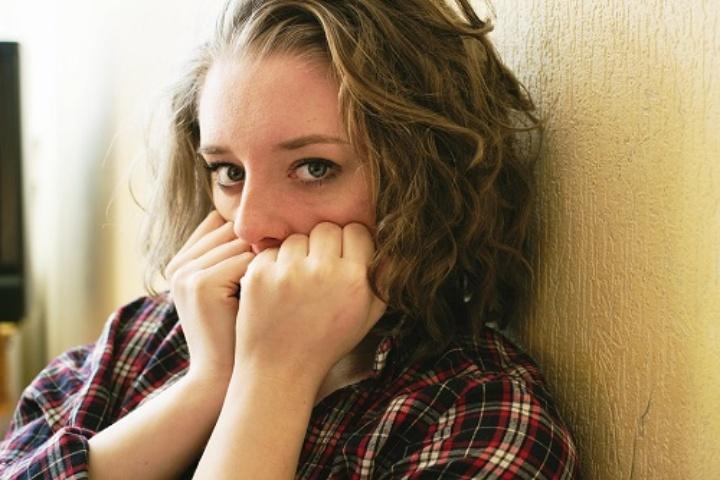 Auf dem Bild sieht man eine junge Frau, die auf dem Boden sitzt und sich an die Wand kauert. Sie hält sich die geballten Hände vor den Mund. Sie wirkt verängstigt.
