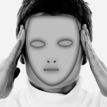 Auf dem Bild ist der Kopf eines Mannes zu sehen. Vor sein Gesicht hält er eine Maske, die ausdruckslos wirkt und wie ein aufgesetztes Gesicht wirkt. Er hält sich die Hände an die Schläfen als würde er sie massieren.