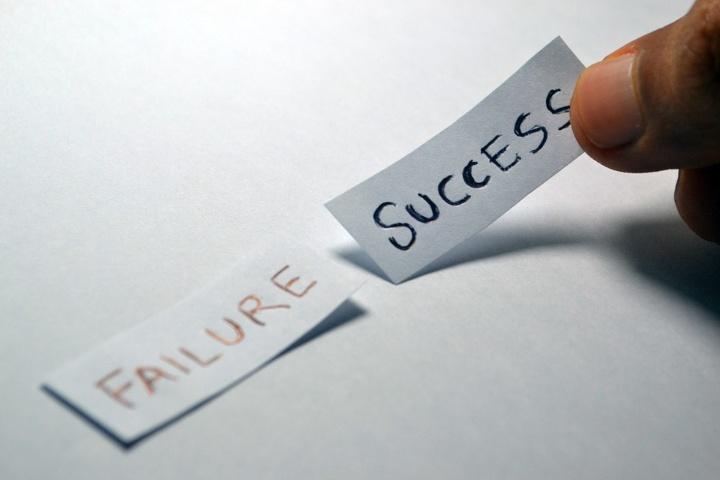 """Symbolbild: Auf einem Tisch liegen zwei Zettel. Auf einem steht """"Failure"""" auf dem anderen steht """"Success"""". Man sieht, wie eine Hand den Zettel mit der Aufschrift """"Success"""" aufhebt."""