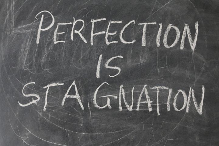 """Auf einer Kreidetafel steht der Satz """"Perfection is stagnation"""" in Gr0ßbuchstaben."""
