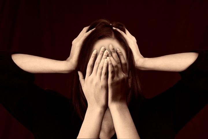 Auf dem Bild ist eine Frau zu sehen. Ihr Gesicht ist mit zwei Händen bedeckt. Gleichzeitig werden zwei Händ über ihre Kopf zusammengeschlagen als raufe sie sich die Haare.