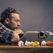 Ein Mann lehnt sich mit verschränkten Armen auf einen Tisch. Vor ihm steht eine Schreibmaschine. Er starrt nachdenklich auf die Schreibmaschine und hat sein Kinn auf seine Armen abgelegt. Neben ihm liegen zerknüllte Papiere.