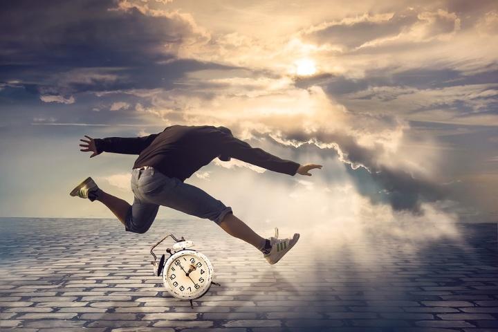Symbolbild: Ein Mann macht einen breiten Satz über eine Uhr hinweg.