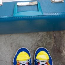 Auf dem Bild sind ein hellblauer Koffer und ein paar gelbe Schuhe zu sehen, die von oben fotografiert sind. Das Bild vermittelt Aufbruchstimmung.