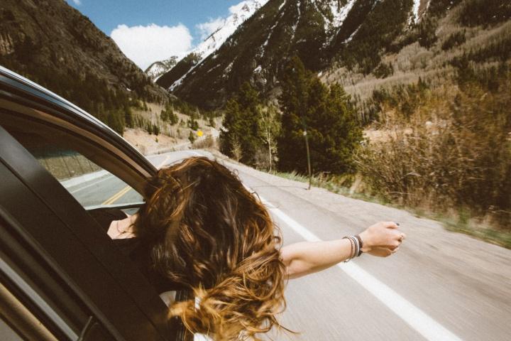 Symbolbild: Man sieht eine junge Frau, die ihren Kopf aus dem Fenster eines fahrenden Autos hält. Der Fahrtwind bläst duch ihr Haar und die Sonne scheint. Das Bild vermittelt ein Gefühl von Freiheit.