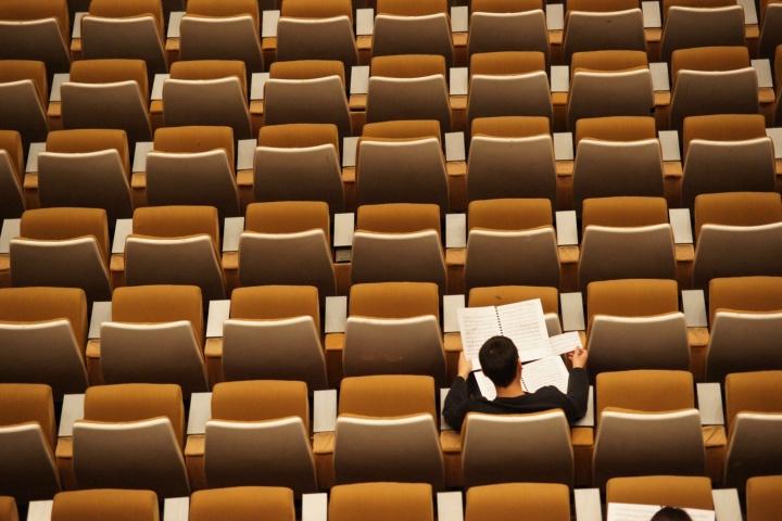 Ein Mann sitzt allein im Publikum