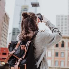 Ein Mädchen fotografiert in einer fremden Stadt.